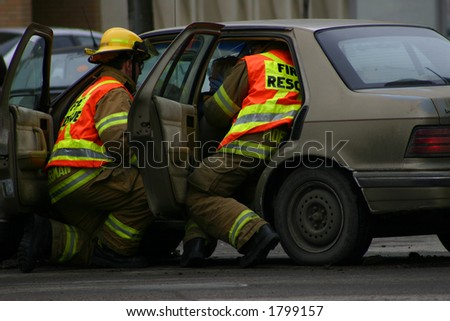 Two firefighters attend to a woman injured in an accident.