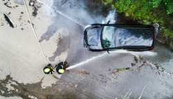 Two firefighters extinguishing a burning car after an accident.