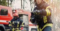 Two firefighters in fire fighting operation, fireman in protective clothing and helmet with equipment in action fighting