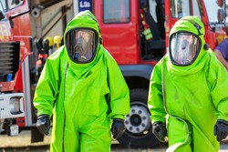 Two firefighters in protective suit for hazardous material durin