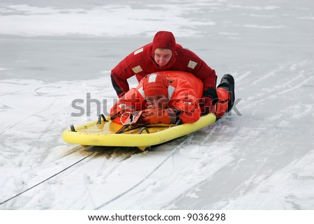 two firemen practicing rescue maneuvers on ice