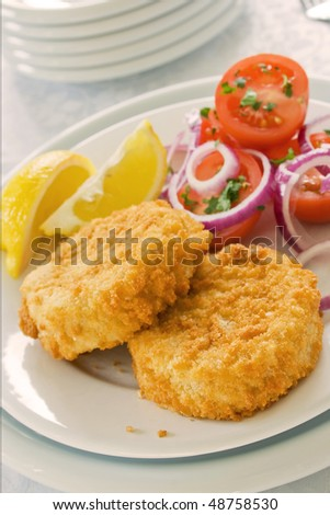 Two fish cakes on a plate with salad and sliced lemons