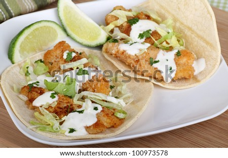 Two fish tacos with sliced lime on a plate