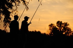 two fisherman at sunset. silhouettes of fishermen