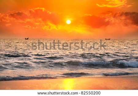 Two Fisherman boats catching fish in the ocean at sunset dramatic sky background in Kerala, India