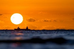 Two fishermen fishing in the sunset on the background of a huge solar disk. Mauritius, the Indian Ocean