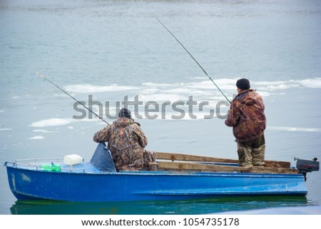 Two fishermen in an old motor boat on the river Don. Spring fishing for Don #1054735178