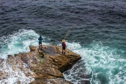 Two Fishermen on a rocky ledge at Bondi Beach, Sydney, Australia.