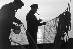 Two fishermen repairing fishing nets
