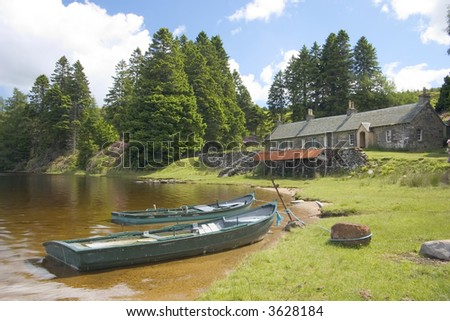 Two fishing boats moored by a row of old fishing lodges beside a scottish loch