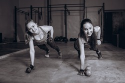 Two fit women in gym doing fitness exercises with dumbbells staying in plank pose, black and white