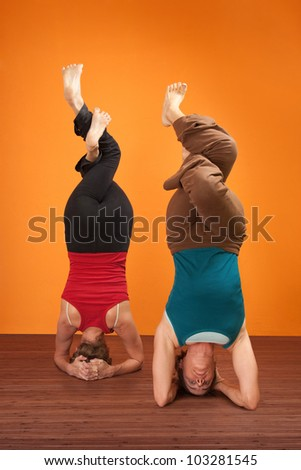 Two fit women in upside down position with interweaved legs
