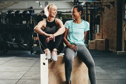 Two fit young female friends in sportswear laughing together while sitting on a box at the gym after a workout session