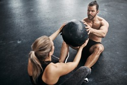 Two fit young people in sportswear sitting on a gym floor working out together with a medicine ball during an exercise session