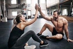 Two fit young people in sportswear smiling and high fiving together while sitting on a gym floor after working out
