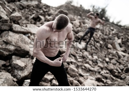 Two fitness strongmen having workout outdoor in a rocky background. Bodybuilders concept background - muscular bodybuilder handsome man doing exercises outdoor. Half naked young men. Bare torso. Man i