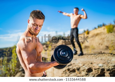 Two fitness strongmen having workout outdoor in a rocky background. Bodybuilders concept background - muscular bodybuilder handsome man doing exercises outdoor. Half naked young men. Bare torso.
