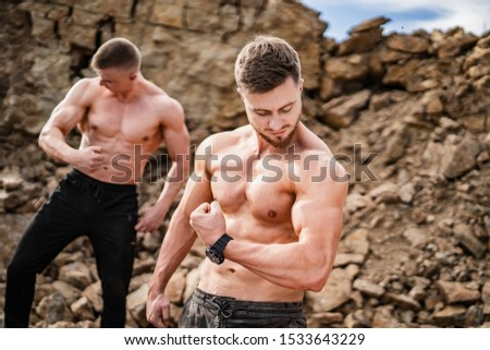 Two fitness strongmen pumping muscles in a rocky background. Bodybuilders concept background - muscular bodybuilder handsome man doing exercises outdoor. Half naked young men. Bare torso.