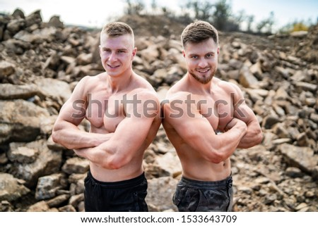 Two fitness strongmen standing back to back with crossed hands in a rocky background. Bodybuilders concept background - muscular bodybuilder handsome man doing exercises outdoor. Half naked young men.