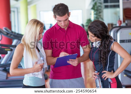 two fitness young women with their coach planned exercises in the gym