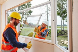 Two fitters from Glaserei build windows when building a house on a construction site