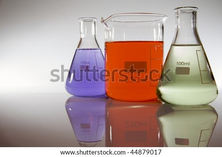 two flasks and a beaker with colored liquid