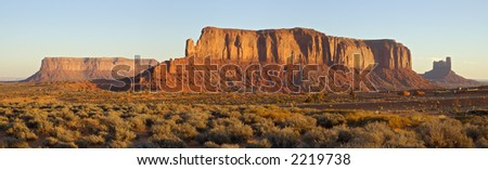 Two flat mesas and a vertical one are sailing through the Monument Valley at cold November dawn, showing off the sediment layers from millions of years ago (Navajo Nation, Utah).