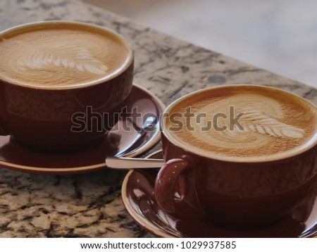 Two flat white coffees made by a barista in mugs with a Rosetta latte art pattern  #1029937585