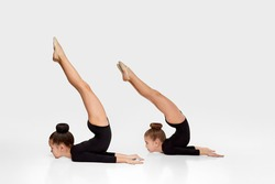 two flexible gymnast child girl in sportswear performs gymnastic exercises on white studio background