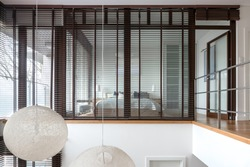 Two floor apartment with bedroom behind window wall with wooden blinds and two ceiling ball lamps