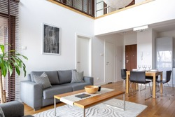 Two-floor apartment with stylish living room with grey sofa and wooden coffee table open to dining area with table for four