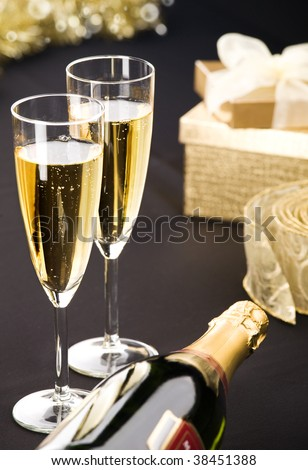 Two flutes and bottle of champagne. Golden gift box and transparent ribbon in background. All on matt black.