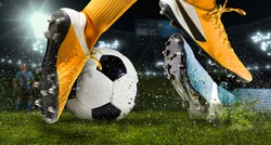 Two football player man in action on dark arena background. Soccer player making sliding tackle