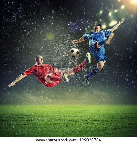 two football players in jump to strike the ball at the stadium