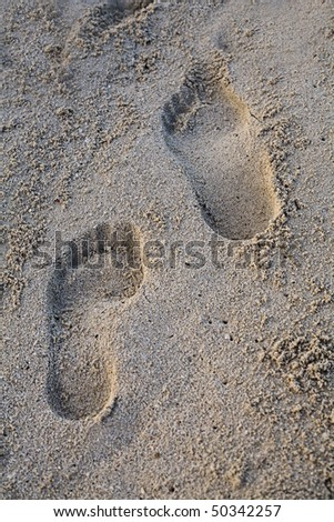 Two footprints in fine white caribbean sand with morning sun