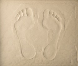 Two footprints on light beige sea sand texture, footstep pattern. Sandy beach textured background with two barefoot prints top view