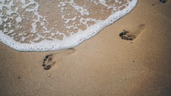 Two footprints on sand at the beach with waves and foam
