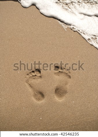 two footprints on sand with white water wave.