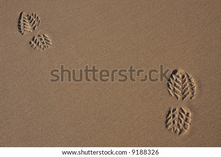 Two footprints on the sand of a beach
