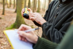 Two foresters with rangefinder and clipboard at the forest care