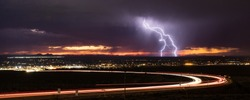 Two forks of cloud to ground lightning strike in the Upper Valley of El Paso, Texas, USA, in August 2019, with curving light trails from Transmountain Road in the foreground.