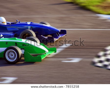 Two formula cars speeding to finish line