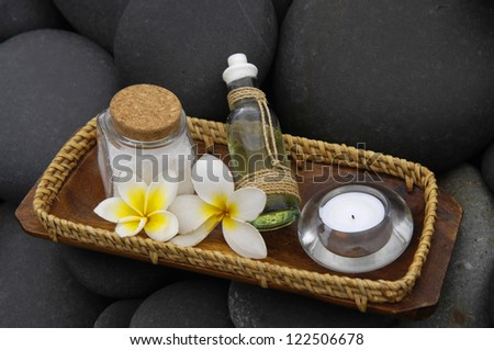 two frangipani and massage oil with candle in bowl on stones