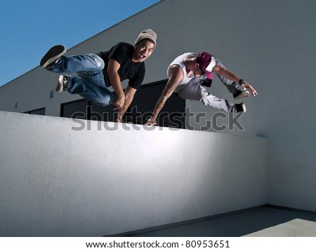 two free-runners jumping over a wall - stock photo