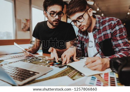 Two Freelance Designers Working Together Indoors. Portrait of Busy Graphic Illustrators Focused on Project Using Notepad, Laptop Sitting at Table. Teamwork Coworking Concept #1257806860
