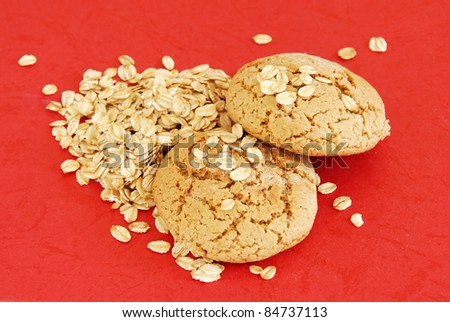 two fresh appetizing oatmeal cookies over red background