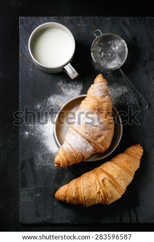 Two fresh baked croissants with sugar powder served with aluminum cup of milk and vintage sieve over black slate background