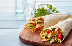 Two fresh chicken and salad tortilla wraps on wooden cutting board with glasses in background