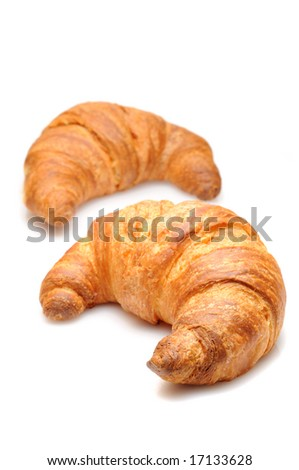 Two fresh croissant isolated over white background - focus on close one - stock photo
