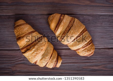 Two fresh croissants on a brown wooden table. View from above. View from above. #1351390583